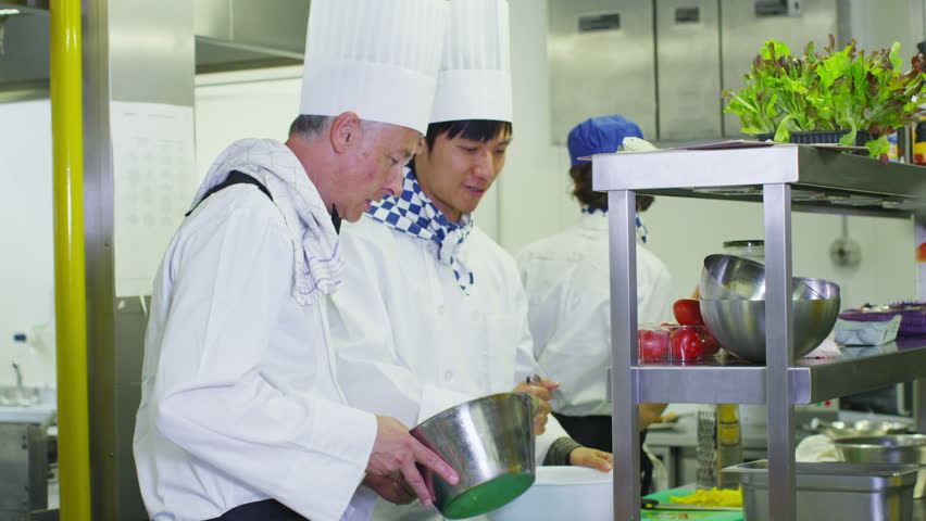 Team of professional chefs preparing food in a commercial kitchen. In slow motion.