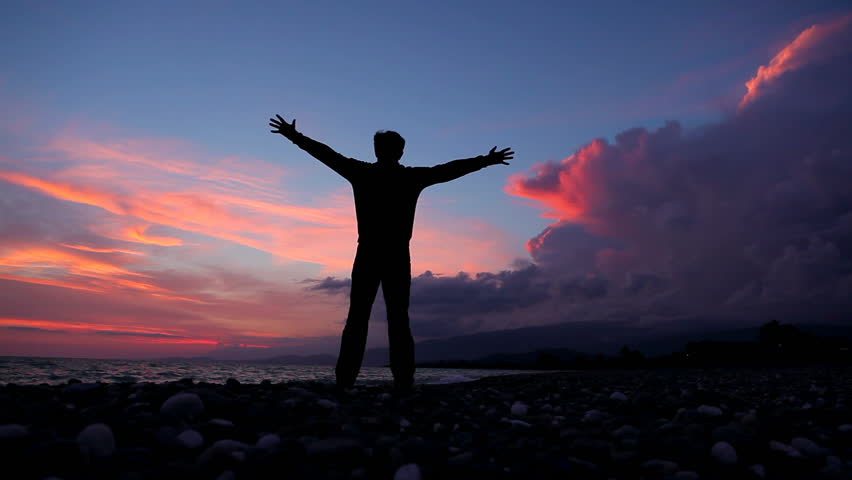 Silhouette of man on the beautiful sunset by the sea. Freedom concept. - HD stock footage clip