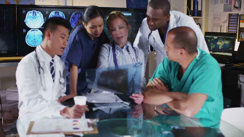 Mixed ethnicity group of medical professionals in a meeting are looking at a patient's x rays and discussing the case. In slow motion.