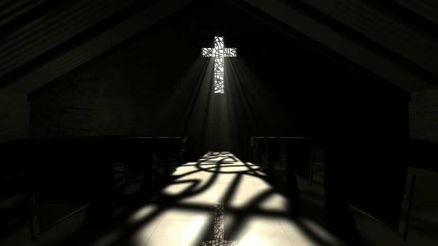 A slow zoom down the aisle of a dark church illuminated by light rays penetrating a crucifix shaped window