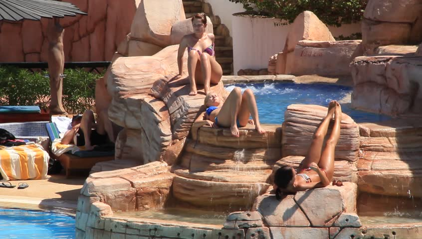 EGYPT, SOUTH SINAI, SHARM EL-SHEIKH, SEPTEMBER 22, 2010: People inside hotel area with blue swimming pool, Sharm El Sheikh, Egypt, September, 22, 2010 - HD stock footage clip