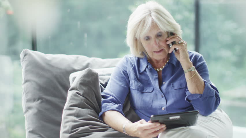 Attractive mature woman making a phone call with a computer tablet in her hand