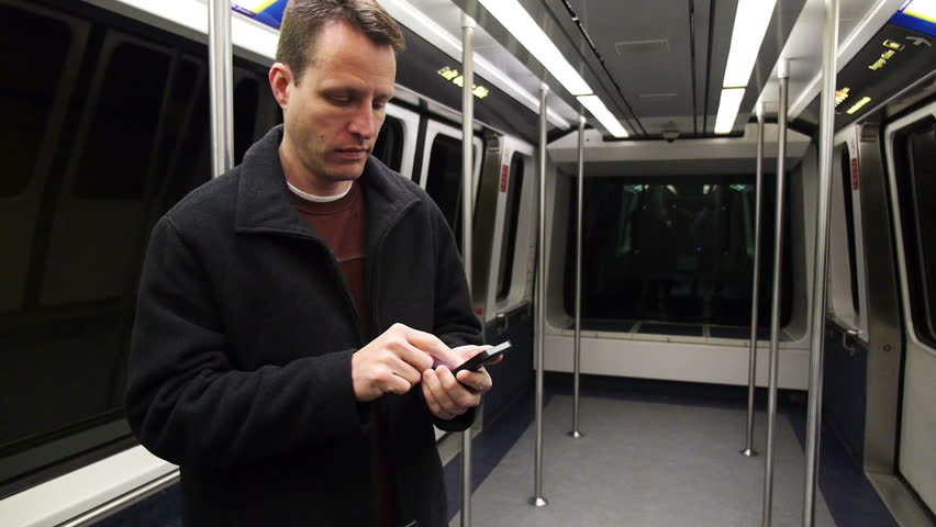 A man uses his smartphone on the subway.