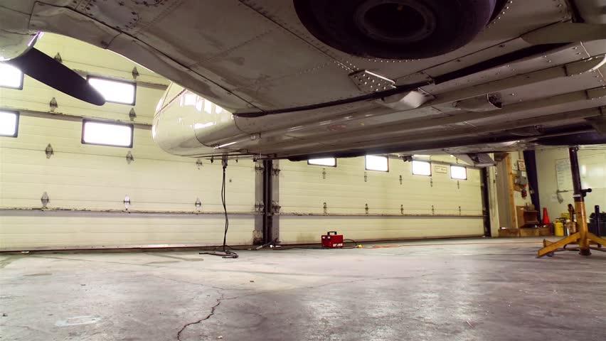 A plane lowers its landing gear in a hangar.