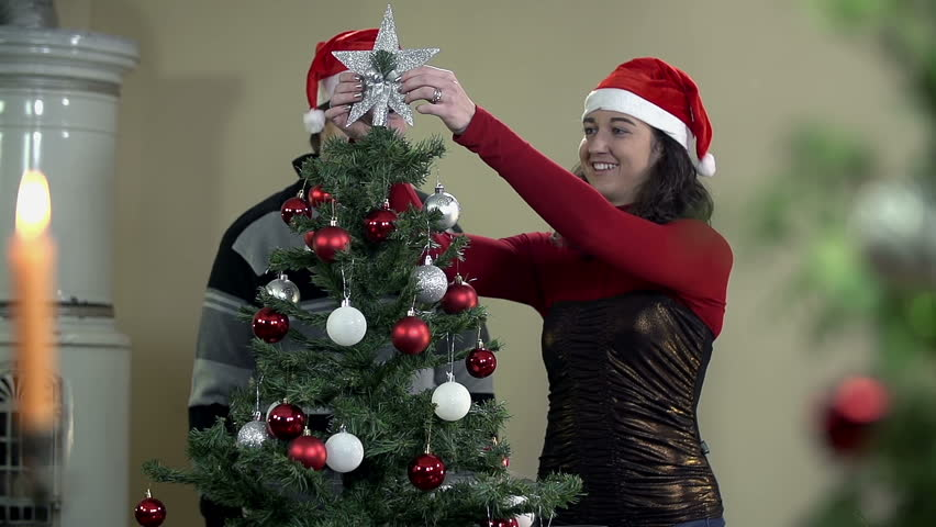 Boy And Girl Enjoying Christmas Tree Decorating In Slow ...