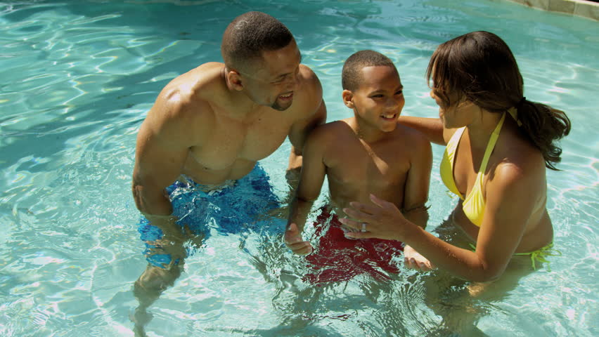 Happy young African American family enjoying healthy swimming lifestyle outdoor pool luxury vacation accommodation overhead shot on RED EPIC, 4K, UHD, Ultra HD resolution - 4K stock video clip