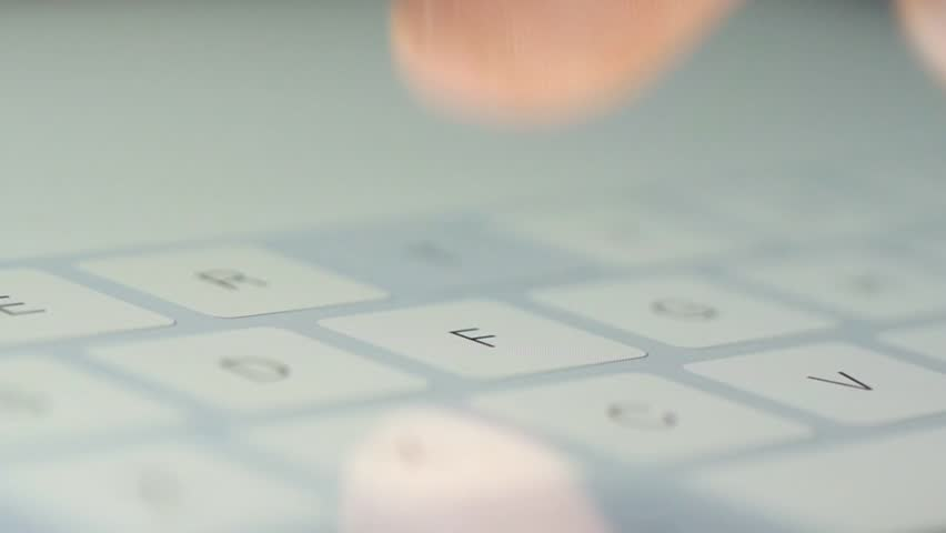 Finger touching virtual keys form a digital keyboard of a touchscreen iPad tablet device. - HD stock video clip