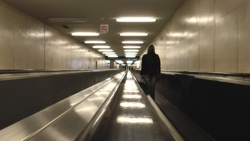 Woman On A Moving Walkway In Montreal Airport - HD stock video clip