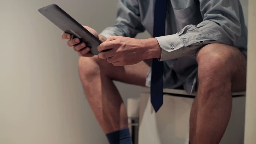 Businessman with tablet computer sitting on toilet