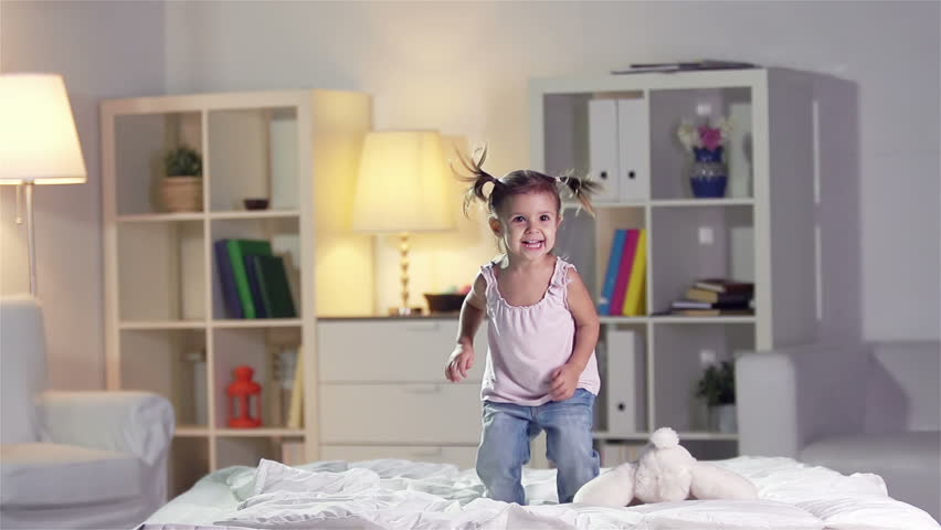 Slow-motion of a carefree girl jumping on the bed - HD stock footage clip