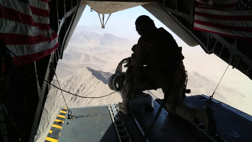 Tail Gunner Sits in Open Doorway of Helicopter over Afghanistan  while U.S. Flags Wave in the Breeze