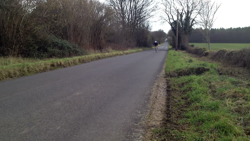 A male road bike cyclist goes past towards camera out of saddle working hard up the slight hill. Model release on file.