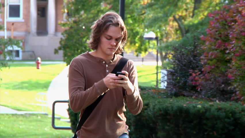 Student texting while walking on campus. - HD stock video clip