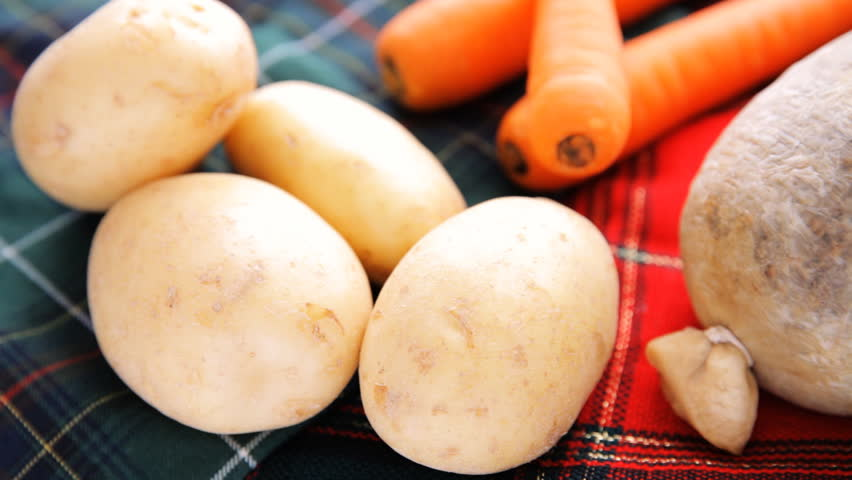 The raw ingredients for a traditional Scottish Robert Burns supper of haggis neeps and tatties or potatoes, swede / rutabaga and carrots against a background of tartan.