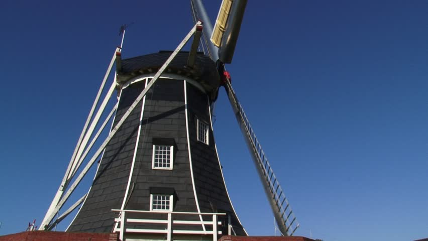 Black tarred windmill - Side view. The beltmolen-type windmill Bataaf dates from 1801 and has been used for milling grain for more than 150 years. WINTERSWIJK, THE NETHERLANDS    - HD stock footage clip