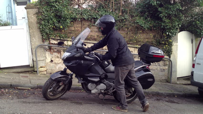 Motorbike courier arrives and dismounts.
