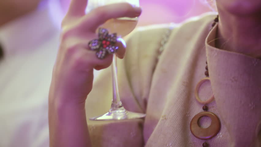 Female hand with beautiful ring holds a glass of champagne - HD stock footage clip