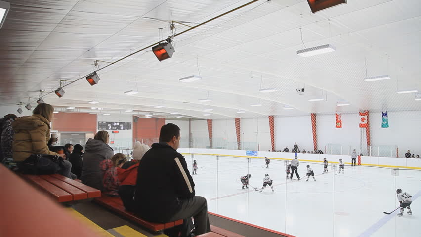OTTAWA - FEBRUARY 2013: Parents watch their children play competitive house league ice hockey in a hockey arena.