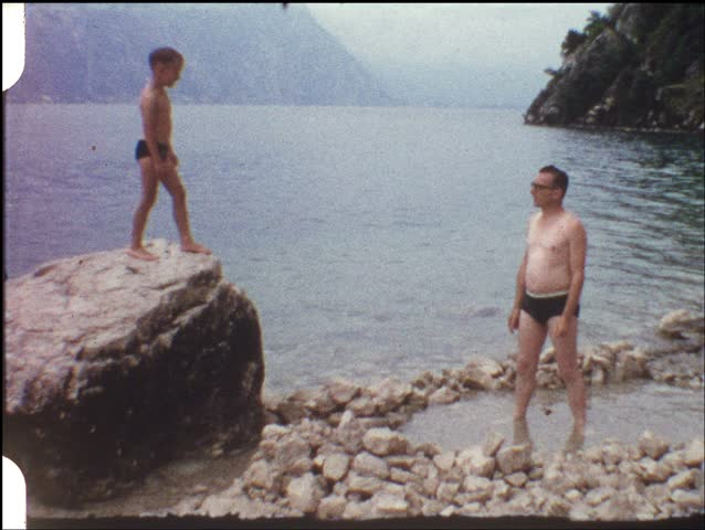 Boy jumping from rock into fathers arms (vintage 8 mm amateur film) - HD stock footage clip