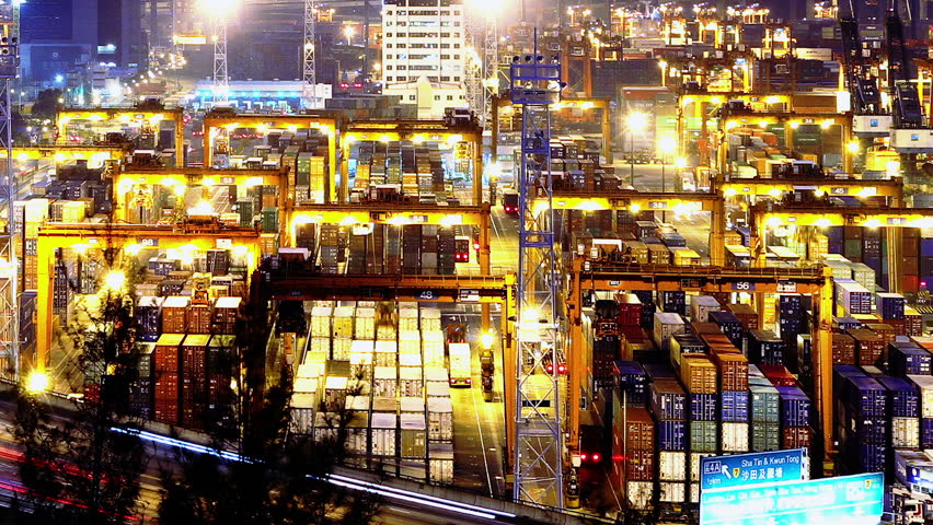 Containers Port Timelapse at Night. Hong Kong. Tight Shot. Cargo containers loading activities in cargo terminal.  Busy traffic across the main road at rush hour. Corporate buildings at the back. - HD stock video clip