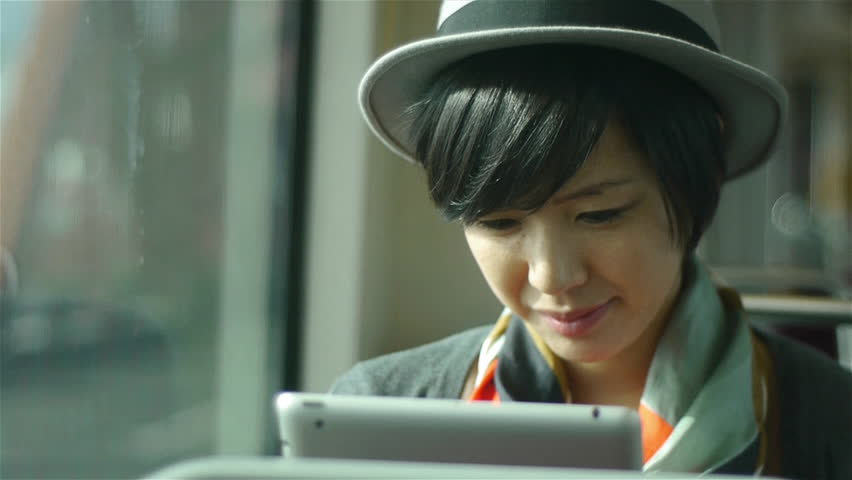 A Woman With A Tablet On A Train Going Over A Bridge, With Background Traffic