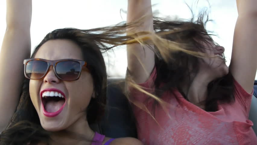 Two Friends Scream With Excitement In The Backseat Of A Convertible