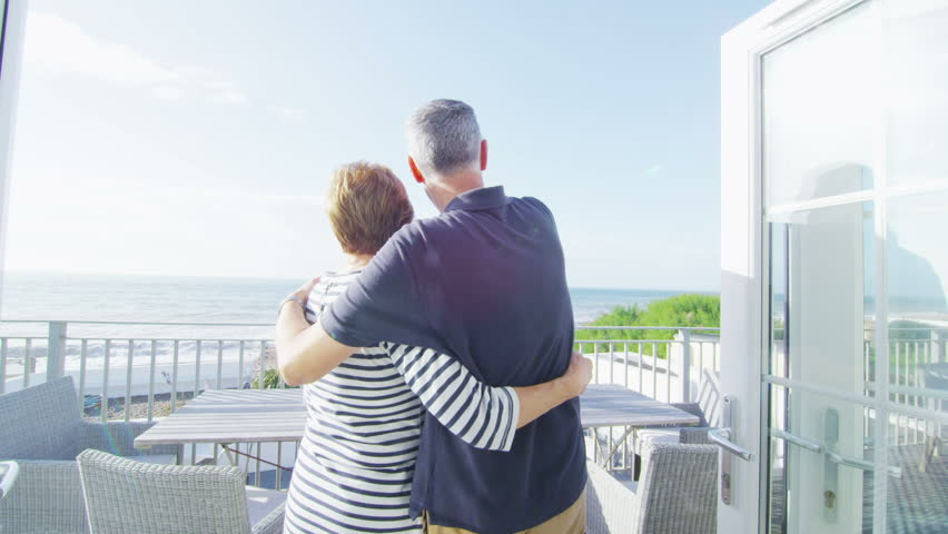 Romantic mature couple in love go to look at the view from the balcony of their beachside apartment. In slow motion.