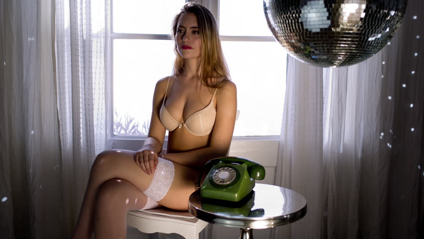 beautiful sexy woman poses and talks on telephone in lingerie in a lounge bathed in sunlight. Useful for fashion, lifestyle and health and beauty