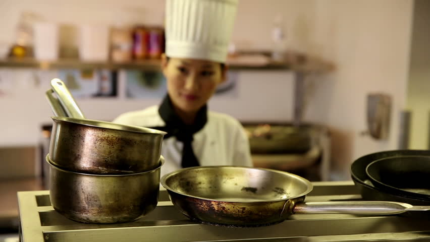 Happy chef taking pots and pans from a shelf in commercial kitchen - HD stock footage clip