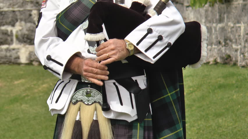 Close up of a Scottish bagpipers hands playing the bagpipes wearing a historic military style uniform of the Gordon tartan.