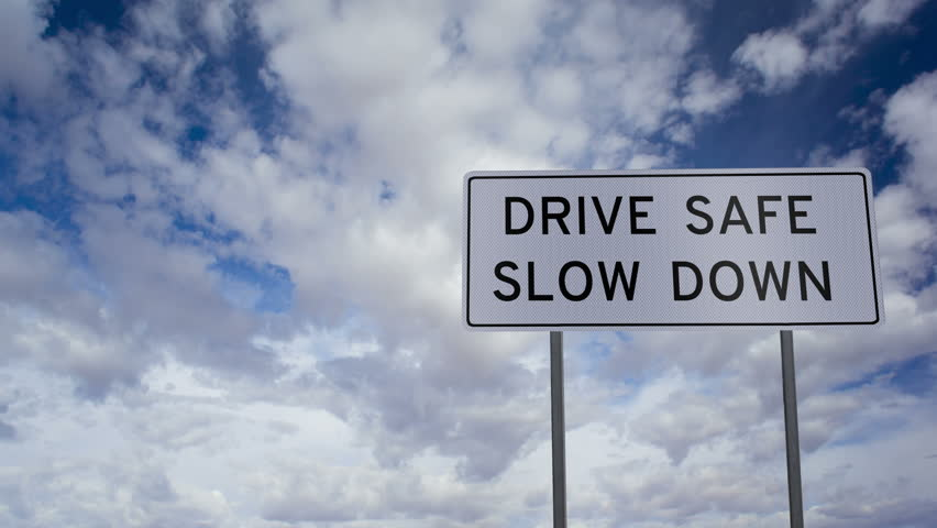 Timelapse clouds background with a highway sign in the foreground that has the words of a safety campaign that says DRIVE SAFE SLOW DOWN on it.