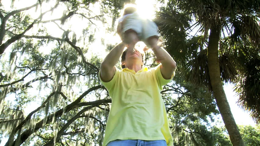 Happy young Caucasian child being held high loving fathers arms fun outing park sun lens flare - Young Caucasian Father Holding Son High Up Arms - HD stock footage clip