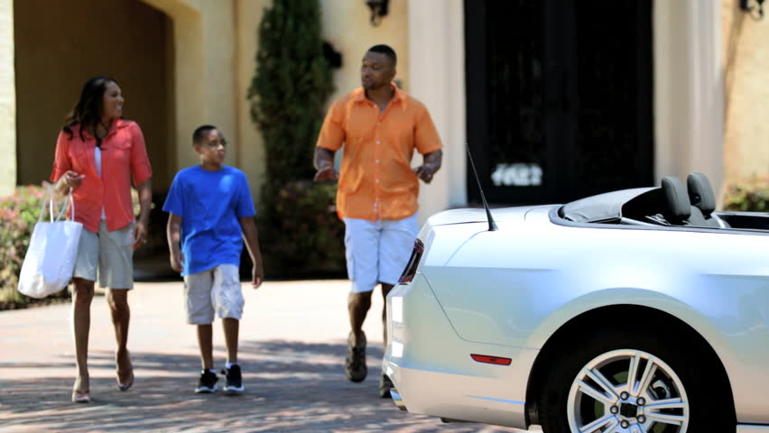 Attractive African American couple young son climbing into family cabriolet convertible to go shopping - Attractive Ethnic Family Cabriolet Shopping Trip