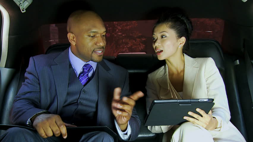 Close up successful multi ethnic male female business people using wireless tablet technology back seat luxury limousine transport - Close Up Smart Business Leaders Wireless Tablet Limousine