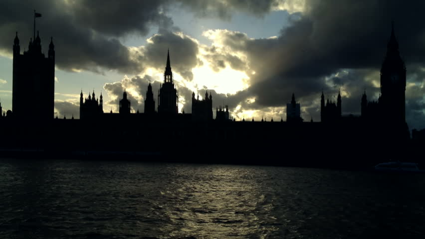 A silhouette of the houses of parliament, Victoria Tower and Big Ben Clock Tower (Elizabeth Tower) at dusk in London in the spring time.