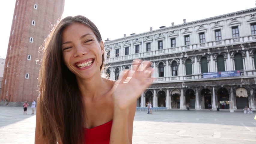Woman waving hands saying hello in Venice. Smiling happy cheerful multiracial girl having fun on San Marco Square, Venice, Italy. Caucasian Asian model looking at camera.