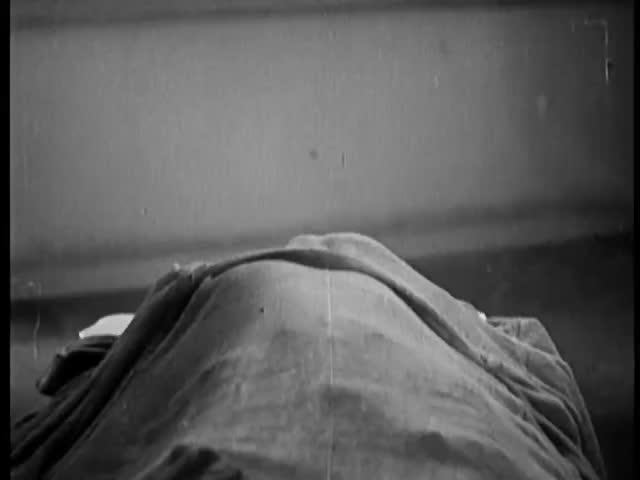 Person hidden under bathrobe rising from bed