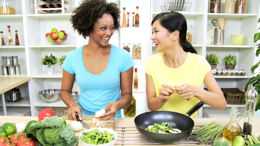 Multi Ethnic Girls Home Kitchen Fresh Stir Fry Vegetables - Young multi ethnic females home kitchen preparing to cook delicious market fresh organic vegetables healthy living stir fry meal