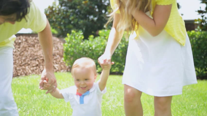 Parents Helping Little Boy Practice Walking Barefoot Park - Healthy happy young male Caucasian child practicing walking grass outdoors park holding parents hands