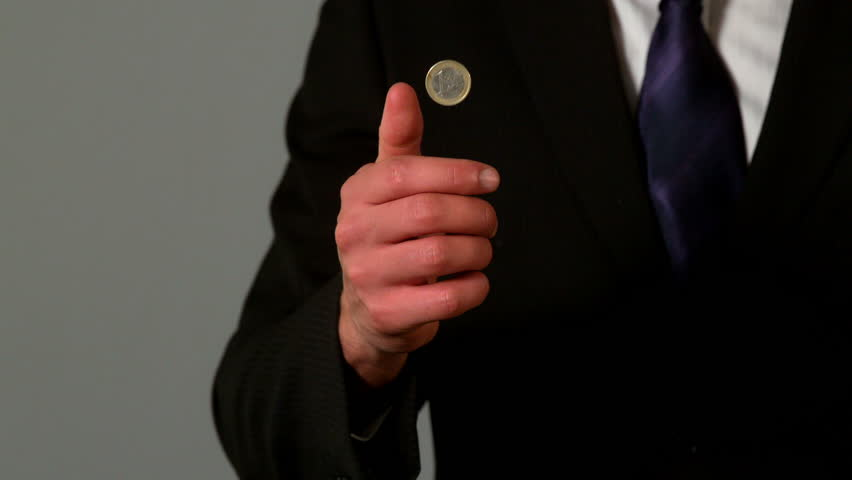 Businessman flipping a euro coin in slow motion