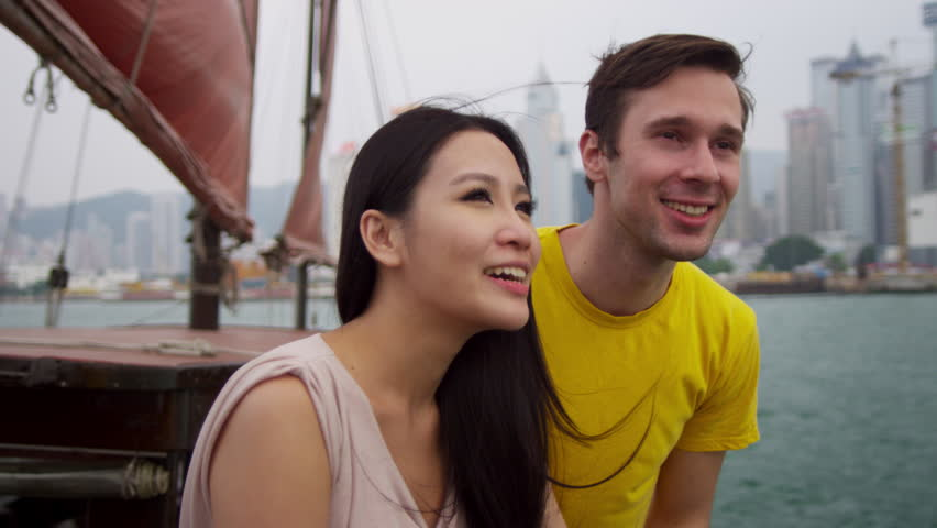Close up happy young multi ethnic heterosexual couple casual vacation clothes together sightseeing Chinese junk shot on RED EPIC