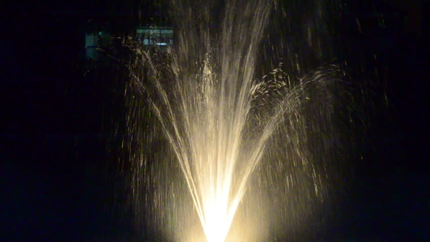 Yellow iluminated fountain on the middle of a lake 3