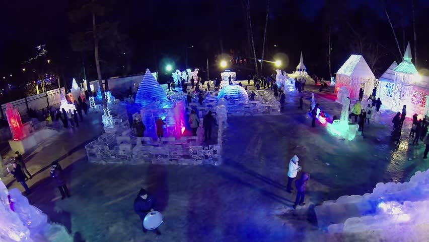 MOSCOW - JAN 1, 2014: Parents with children walk around Ice Town in Sokolniki Park at winter night. Aerial view