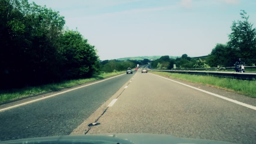 A fast time lapse recording of a car travelling at speed in the outside lane of a dual carriageway, freeway, motorway.