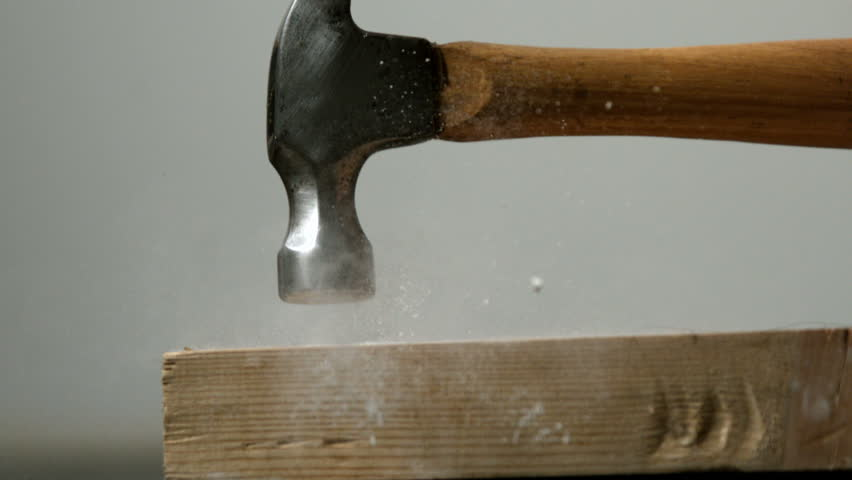 Hammer hitting a nail into wooden plank in slow motion