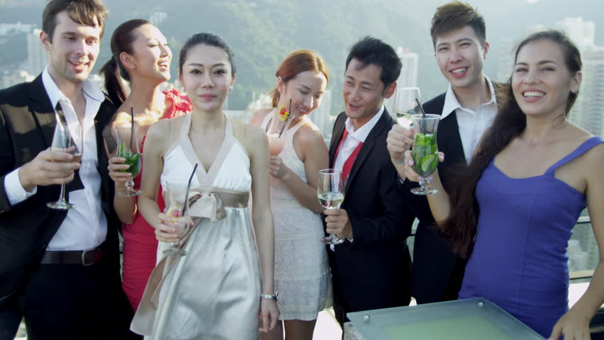 Successful young male female Asian Chinese Caucasian business associates dressed evening clothes enjoying evening drinks luxury rooftop bar city downtown shot on RED EPIC