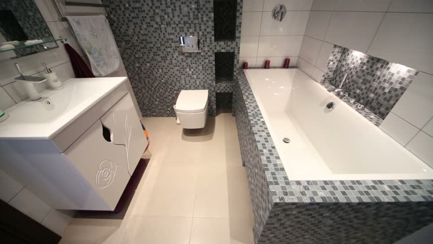 Interior of full bathroom with bath, washbasin, toilet bowl, towel dryer.