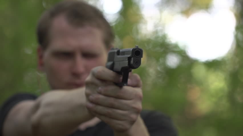 Man wearing ear plugs fires a high caliber pistol in woodland.  Muzzle flashes visible.  Recorded in slow motion at 480fps. - HD stock footage clip