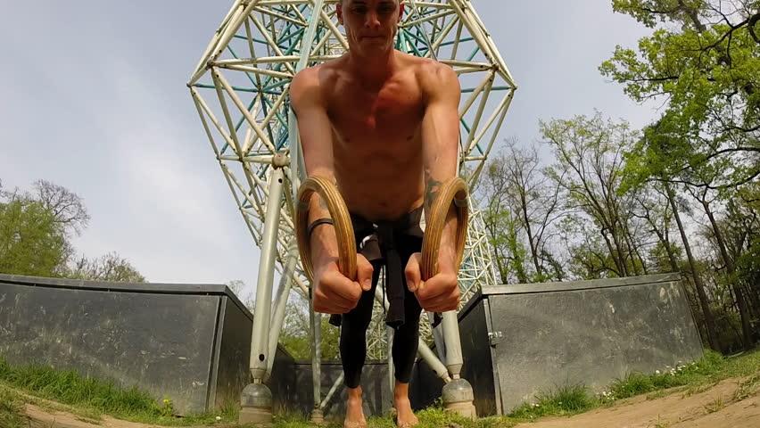 Muscular man is doing push-ups on gymnastics rings