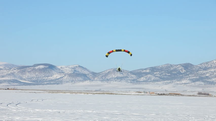 Powered parachute doing a touch and go on ice and snow covered lake in winter. Central Utah winter recreation and sport. Second PPC flying in background. - HD stock footage clip
